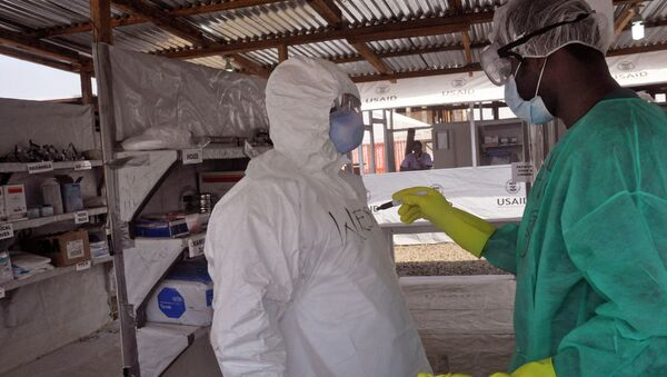 A health care worker assists a collegue inside a USAID, funded Ebola clinic in Monrovia, Liberia, Friday, Jan. 30, 2015. The World Health Organization says officials are now focused on ending the biggest-ever Ebola outbreak rather than just slowing the virus' spread. In an update published Thursday, Jan. 29, 2015, the U.N. health agency said the three most affected countries _ Guinea, Sierra Leone and Liberia _ reported fewer than 100 cases in the past week, for the first time since June, 2014. - Sputnik International