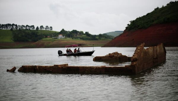 Tourists drive a boat past the walls of the old school of the re-emerging old city of Igarata in the Jaguari reservoir, Sao Paulo State, February 4, 2015 - Sputnik International
