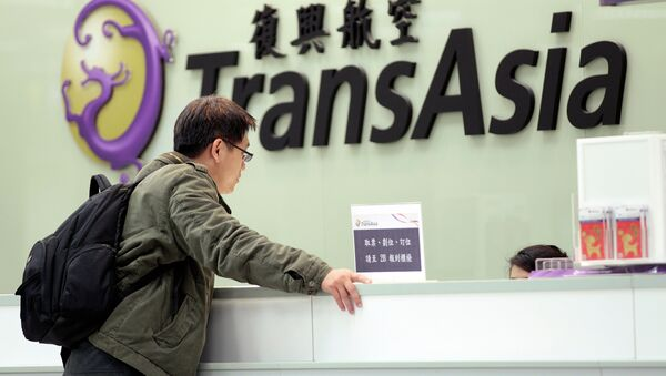 A passenger waits at the ticket counter of TransAsia Airways at the Songshan Airport in Taipei, Taiwan, Saturday, Feb. 7, 2015 - Sputnik International