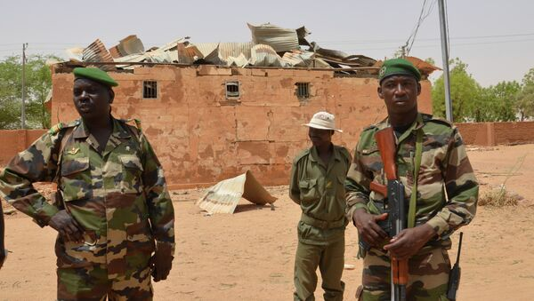Nigerien soldiers stand near a damaged building in an army base in Agadez, northern Niger on May 26, 2013 - Sputnik International