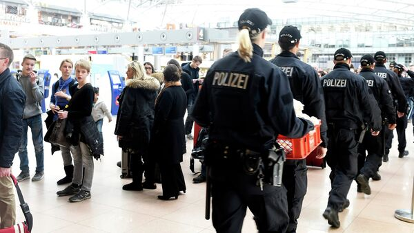 Police officers pass a row of waiting passengers during a strike of security employees at the airport Fuhlsbuettel in Hamburg, February 9, 2015 - Sputnik International