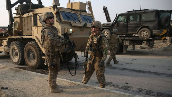 U.S. and British soldiers chat at the site of a suicide attack in Kabul, Afghanistan in January. - Sputnik International