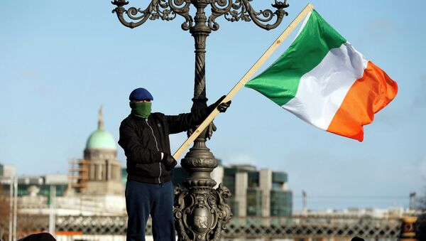 A demonstrator waves the national flag as people gather to protest against austerity policies and increases in water bills, according to local media, in central Dublin - Sputnik International