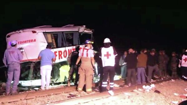 In this image made from Associated Press Television News video emergency responders work at the scene of a bus and freight train collision Friday Feb. 13, 2015. The collision at a grade crossing in northern Mexico, killed at least 16 people and injured 22, according to a Mexican official. The official said the accident Friday occured in the town of Anahuac, which is Tamaulipas state near the border city of Nuevo Laredo, across from Laredo, Texas. - Sputnik International