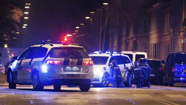 Police officers take cover behind their patrol cars on the streets of central Copenhagen on February 15, 2015 - Sputnik International