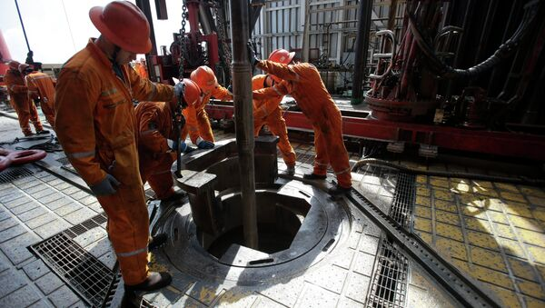 Oil workers lower the drill on the Centenario deep-water drilling platform off the coast of Veracruz, Mexico in the Gulf of Mexico, Friday, Nov. 22, 2013 - Sputnik International