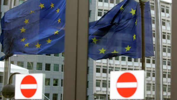 The EU blacklist targets a total of 19 individuals from Ukraine and Russia. Above: The EU nations flags are mirrored in the windows of the EU Council headquarters. - Sputnik International