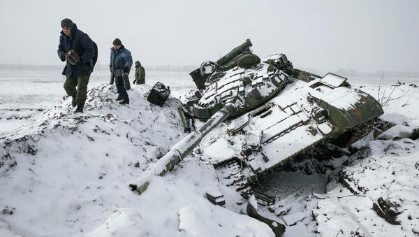 Members of the self-proclaimed Donetsk People's Republic army collect parts of a destroyed Ukrainian army tank in the town of Vuhlehirsk, about 10 km (6 miles) to the west of Debaltseve, February 16, 2015 - Sputnik International