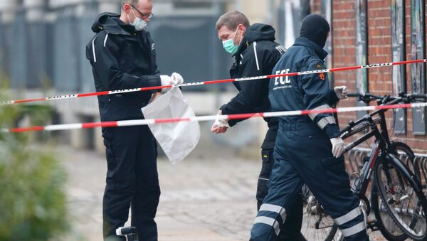 Danish police investigate the area where an unattended package was found in front of a cafe in Oesterbro, Copenhagen February 17, 2015 - Sputnik International