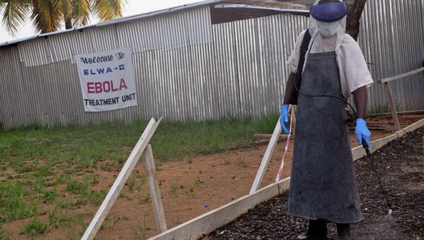 A health care worker sprays disinfectant outside a USAID, funded Ebola clinic in Monrovia, Liberia, Friday, Jan. 30, 2015 - Sputnik International