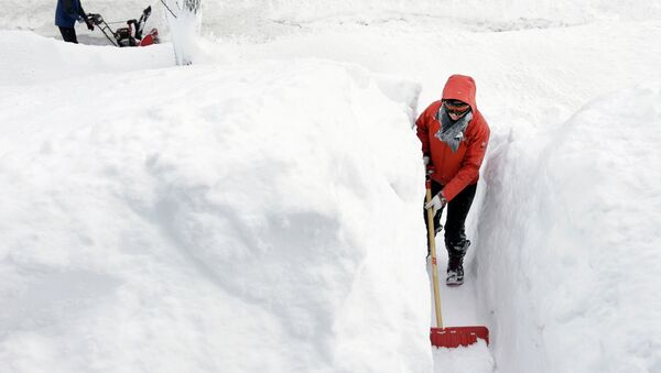 Kim Taylor, of Norwood, Mass., right, shovels a path in the snow in front of her home Sunday, Feb. 15, 2015, in Norwood. A storm brought a new round of wind-whipped snow to New England on Sunday, threatening white-out conditions in coastal areas and forcing people to contend with a fourth winter onslaught in less than a month. - Sputnik International