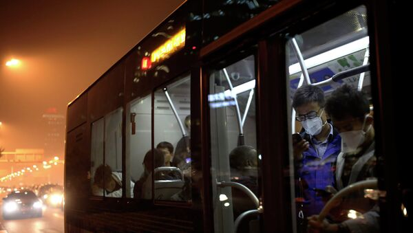 Commuters wearing masks to protect themselves from pollutants check smartphones as they ride on a bus on a hazy day in Beijing, China Monday, Oct. 20, 2014 - Sputnik International