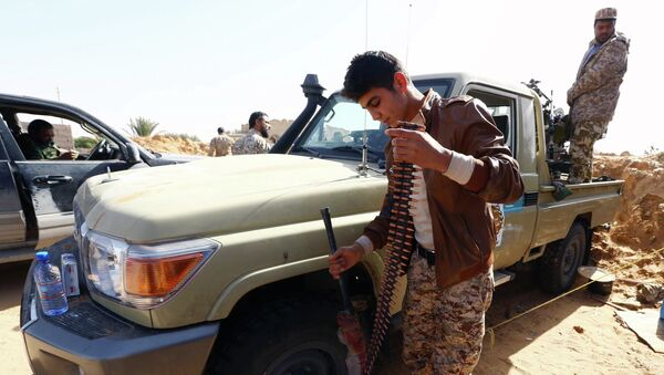 Fighters from the Fajr Libya (Libya Dawn) militia hold a position during clashes with forces loyal to Libya's internationally recognised government as they fight for the control of the area near the Wetia military air base on February 4, 2015 in al-Aqrabiyah, some 170 kilometres west of the capital Tripoli - Sputnik International