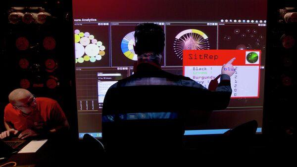 A representative of GCHQ points to a screen - Sputnik International