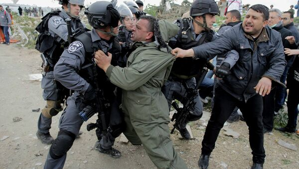 A Palestinian man scuffles with Israeli border policemen as they clear a protest on land that Palestinians said was confiscated by Israel for Jewish settlements, near the West Bank town of Abu Dis near Jerusalem - Sputnik International