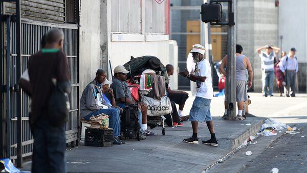 Men sit along a street in Skid Row in Los Angeles, California - Sputnik International