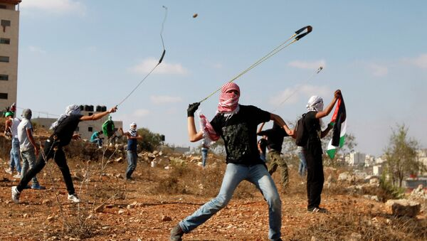 Palestinians throw stones during clashes with Israeli soldiers on the 13th anniversary of the second Palestinian Intifada. - Sputnik International