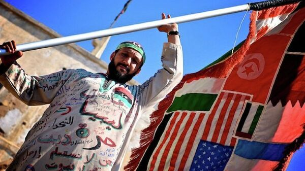 A man holds a flag of countries involved in the Libyan Civil War. - Sputnik International
