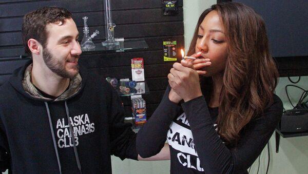 Peter Lomonaco, co-founder of the Alaska Cannabis Club, and CEO Charlo Greene, share a joint at their medical marijuana dispensary in Anchorage, Alaska. - Sputnik International