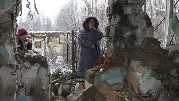 Local residents standing at what has remained of their house after another artillery shelling of Donetsk. - Sputnik International