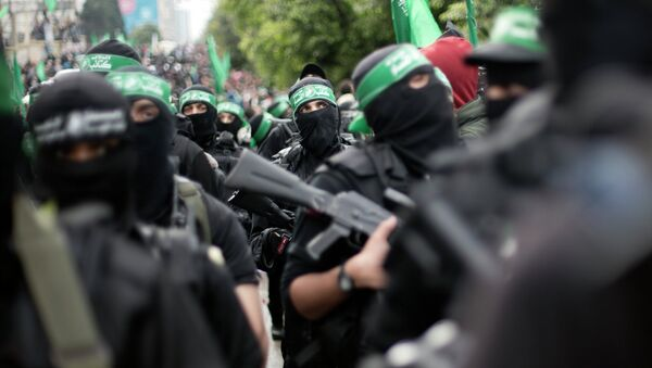 Palestinian Hamas masked gunmen display their military skills during a rally to commemorate the 27th anniversary of the Hamas militant group, in Gaza City, Sunday, Dec. 14, 2014 - Sputnik International