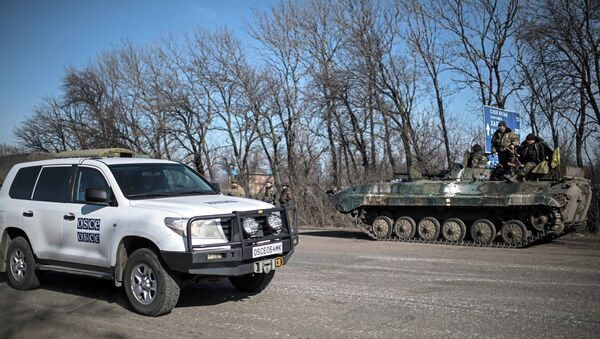 A car of Organization for Security and Co-operation in Europe (OSCE) mission drives past a Ukrainian military vehicle near Artemivsk, eastern Ukraine - Sputnik International