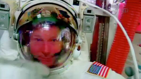 In this screenshot from a video provided by NASA, astronaut Terry Virts points to his helmet as he sits inside the International Space Station Wednesday during an inspection for water in his suit. - Sputnik International