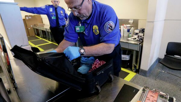 A TSA agent checks a bag at a security checkpoint area at Midway International Airport in Chicago. - Sputnik International