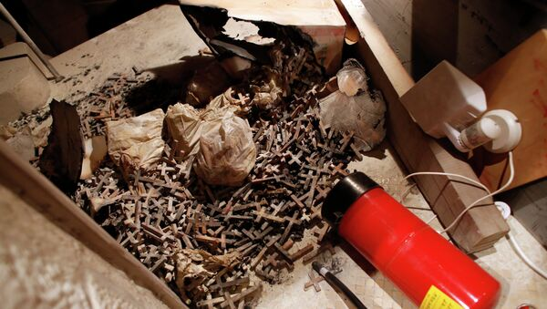 A picture taken on May 26, 2014 shows burnt wooden crosses and a fire extinguisher after arsonists set fire to a small section of the Church of the Dormition - Sputnik International