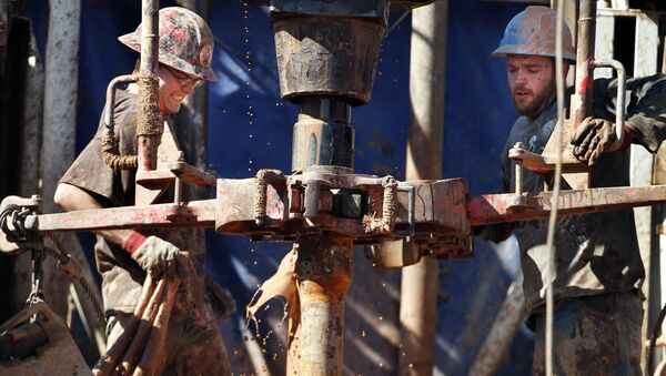 Oil field workers drill into the Gypsum Hills near Medicine Lodge, Kan. Plunging crude prices are hitting oil producers especially hard in places like Kansas - Sputnik International