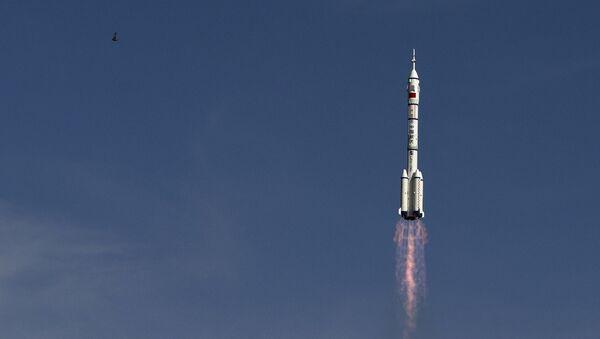 The Long March 2F rocket carrying the Shenzhou 10 capsule blasts off from the Jiuquan Satellite Launch Center as a bird flies, in Jiuquan, northwest China's Gansu Province - Sputnik International
