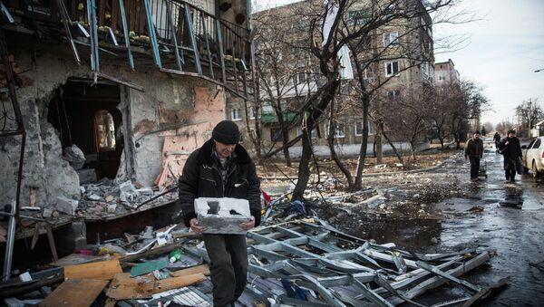 A man salvages cinder blocks from a destroyed building on February 25, 2015 in Debaltseve, Ukraine - Sputnik International
