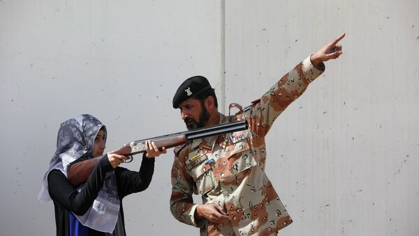 Pakistan Rangers soldier gestures as he instructs a female student of Nadirshaw Eduljee Dinshaw (NED) University during a counter-terrorism training demonstration at the Rangers Shooting & Saddle Club (RSSC) on the outskirts of Karachi, February 24, 2015 - Sputnik International