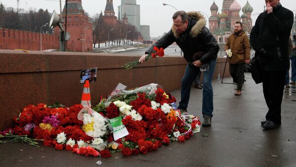 People come to lay flowers at the site, where Boris Nemtsov was shot dead, with St. Basil's Cathedral (R) and the Kremlin walls seen in the background, in central Moscow, February 28, 2015. - Sputnik International