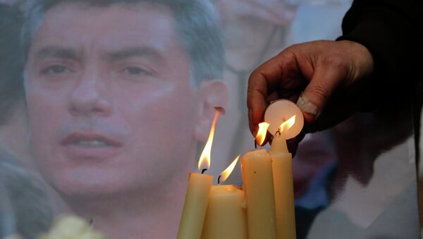 People light candles in memory of Boris Nemtsov, seen behind, at the monument of political prisoners 'Solovetsky Stone' in central St.Petersburg, Russia, Saturday, Feb. 28, 2015. - Sputnik International