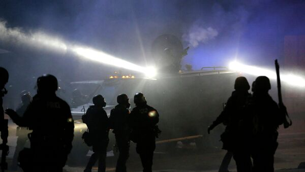 Police in riot gear stand around an armored vehicle as smoke fills the streets Tuesday, Nov. 25, 2014, in Ferguson, Mo. - Sputnik International