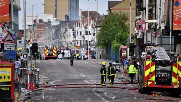 Croydon road looking like a tornado swept up it as fire tenders spray water twelve hours after the fires were set during riots in 2011.  - Sputnik International