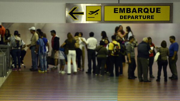 People queue with their luggage at the departure area of the Maiquetia international airport that serves Caracas on July 3, 2014 - Sputnik International