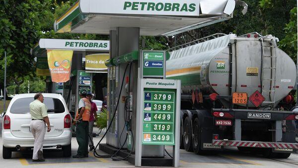 A man fuels up his car at a Petrobras station in downtown Rio de Janeiro - Sputnik International
