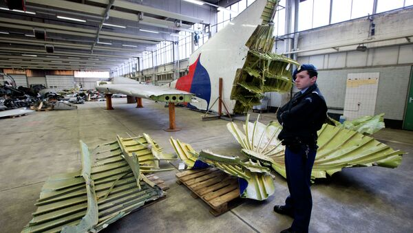 Dutch military police stand next to parts of the wreckage of the Malaysia Airlines Flight 17, displayed in a hangar at Gilze-Rijen airbase, Netherlands, Tuesday, March 3, 2015 - Sputnik International