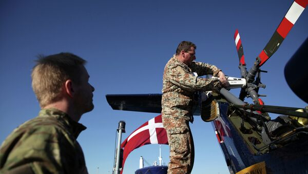 Danish soldiers from the Royal Danish Navy work at an helicopter onboard of the Absalon military ship in the Cypriot port city of Limassol - Sputnik International
