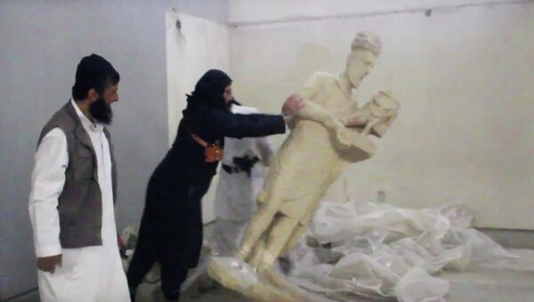 In this image made from video posted on a social media account affiliated with the Islamic State group on Thursday, Feb. 26, 2015, which has been verified and is consistent with other AP reporting, a militant topples an ancient artifact in the Ninevah Museum in Mosul, Iraq - Sputnik International