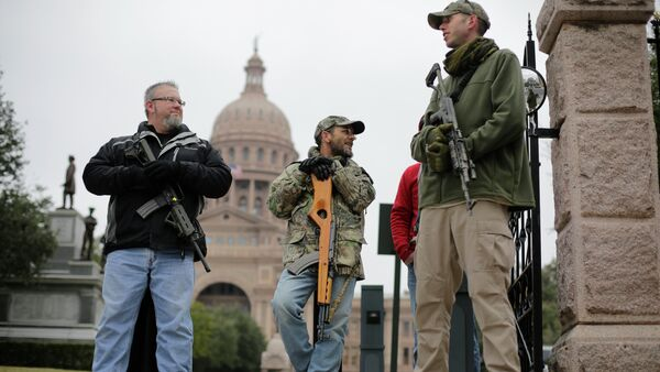 In this 13 January 2015 file photo, gun rights advocates carry rifles while protesting outside the Texas Capitol in Austin, Texas - Sputnik International