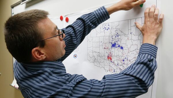 June 26, 2014 file photo, Austin Holland, research seismologist at the Oklahoma Geological Survey, hangs up a chart depicting earthquake activity at their offices at the University of Oklahoma in Norman, Okla - Sputnik International