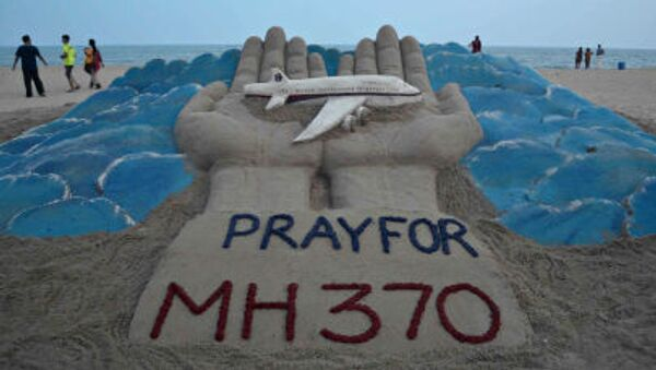 Beachgoers walk past a sand sculpture made by Indian sand artist Sudersan Pattnaik with a message of prayers for the missing Malaysian Airlines flight MH370 - Sputnik International