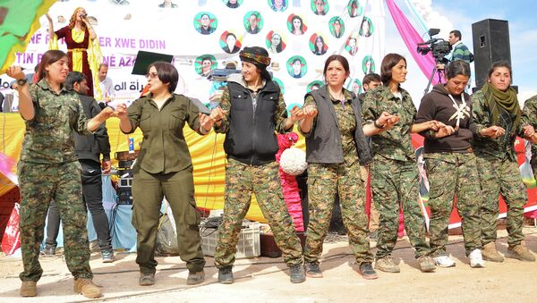 Women fighters from the People's Protection Units (YPG) dance during festivities on the eve of International Women's Day in Syria's northeastern city of Qamishli in the Hasakeh province, on the border with Turkey - Sputnik International