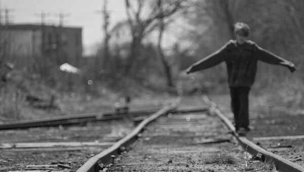 A boy balances on a train rail while walking along tracks - Sputnik International