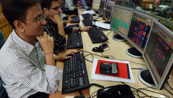 Indian stock dealers watch stock prices on their screen during intra-day trade at a brokerage house in Mumbai - Sputnik International