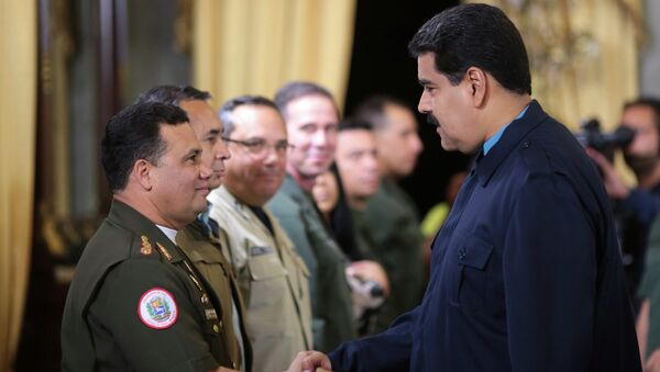 Venezuela's President Nicolas Maduro (R) greets Gustavo Gonzalez as he welcomes army members sanctioned by the U.S. during a national TV broadcast in Caracas in this March 9, 2015 picture provided by Miraflores Palace. - Sputnik International