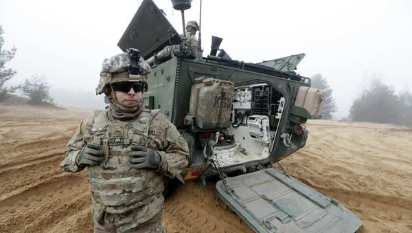 Soldiers of the U.S. Army's 2nd Cavalry Regiment, deployed in Latvia as part of the US Operation Atlantic Resolve, are pictured near their armored vehicle named Stryker during a joint military exercise in Adazi, Latvia - Sputnik International